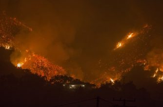 CARPINTERIA, CA - DECEMBER 10: Flames come close to a house as the Thomas Fire advances toward Santa Barbara County seaside communities on December 10, 2017 in Carpinteria, California. The Thomas Fire has grown to 173,000 acres and destroyed at least 754 structures so far. Strong Santa Ana winds have been feeding major wildfires all week, destroying houses and forcing tens of thousands of people to evacuate.   David McNew/Getty Images/AFP