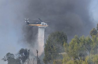 A helicopter drops water over a house on a hilltop in Bel Air, east of the 405 freeway on December 6, 2017 in Los Angeles, California. California motorists commuted past a blazing inferno as wind-whipped wildfires raged across the Los Angeles region, with flames  triggering the closure of a major freeway and mandatory evacuations in an area dotted with mansions. / AFP PHOTO / FREDERIC J. BROWN