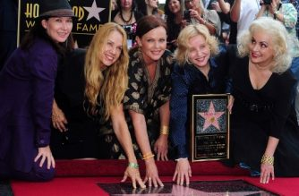 """(FILES) This file photo taken on August 11, 2011 shows The Go-Go's posing beside their star on Hollywood's Walk of Fame in Hollywood. Group members (L to R) Kathy Valentine, Charlotte Caffey, Belinda Carlisle, Gina Schock and Jane Wiedlin received the 2,444th star at The Masque nightclub where they played their first show in 1978.  The Go-Gos, the pioneering all-woman rock band, are heading to Broadway, with an assist by actress Gwyneth Paltrow. The Hollywood star was announced on December 12, 2017, as a producer for """"Head Over Heels,"""" an upcoming musical that will trace the story of the rockers known for infectious pop-rock songs such as """"Vacation."""" / AFP PHOTO / Frederic J. BROWN"""