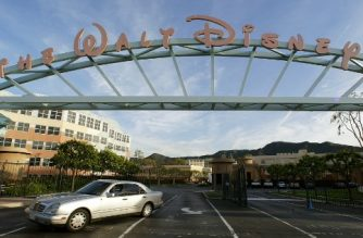 (FILES) This file photo taken on March 3, 2004 shows  a car leaving the main entrance to the Walt Disney Co. office and studio complex in Burbank, California. Walt Disney Co. and 21st Century Fox shares were in the spotlight on December 13, 2017, amid reports the two media-entertainment powerhouses were readying a major deal. The Wall Street Journal reported the deal -- in which Disney would acquire the famed Fox Hollywood studios and key television operations of the Murdoch family-controlled group -- could be announced as early as Thursday.  / AFP PHOTO / ROBYN BECK