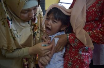 An Indonesian girl cries as she receives a vaccination shot against diphtheria at a village clinic in Jakarta on December 11, 2017.  / AFP PHOTO / ADEK BERRY