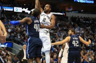 Kawhi Leonard #2 of the San Antonio Spurs takes a shot against Harrison Barnes #40 of the Dallas Mavericks at American Airlines Center on December 12, 2017 in Dallas, Texas.  Ronald Martinez/Getty Images/AFP