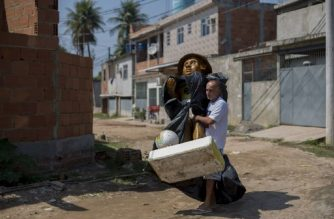 Construction worker Jose Luis Farias da Silva, 56, carries a statue of his two-year-old son Maicon - who was killed by a stray bullet in 1996 while playing outside his house - through the streets of the Complexo do Amarelinho favela or shantytown in Rio de Janeiro, Brazil, on August 28, 2017.  AFP PHOTO / MAURO PIMENTEL