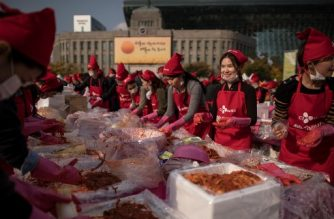Participants make kimchi during an annual kimchi-making festival in central Seoul on November 3, 2017. The kimchi produced during the event is distributed among South Korea's poorer households, and traditionally marks the start of the winter season. / AFP PHOTO / Ed JONES