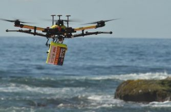 Photo taken on December 10, 2017 shows a shark-spotting drone with a safety flotation device attached underneath flying over Bilgola beach north of Sydney.  High-tech shark-spotting drones are patrolling dozens of Australian beaches this summer to quickly identify underwater predators and deliver safety devices to swimmers and surfers faster than traditional lifesavers.  / AFP PHOTO / PETER PARKS