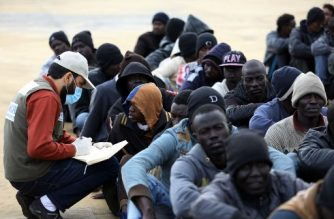 Illegal immigrants sit at a naval base in Tripoli on December 16, 2017, after they were rescued off the coast of Garabulli, 60 kilometers (40 miles) east of the Libyan capital. / AFP PHOTO / Mahmud TURKIA