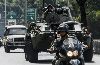 "A an armoured tank from the Venezuelan army drives along a highway in Caracas as an operation to capture Oscar Perez, the Venezuelan helicopter pilot who dropped grenades on the Supreme Court last year during anti-government protests, is carried out on January 15, 2018. Several people, including two police officers, were killed in an operation to capture Oscar Perez, A ministry statement said members of a ""terrorist cell"" were killed, and five were arrested in the operation, but did not say whether the pilot, was among the dead or detained. / AFP PHOTO / JUAN BARRETO"