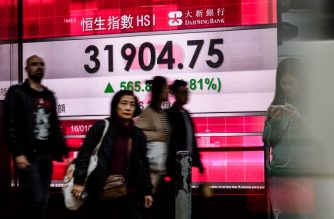 FILE PHOTO: Pedestrians walk past a stocks display board after the Hang Seng Index leapt 1.81 percent, or 565.88 points, to close at 31,904.75 in Hong Kong on January 16, 2018.  Hong Kong stocks posted their highest ever close on January 16, boosted by a flood of cash from mainland Chinese investors and a worldwide surge in optimism about the global economy. / AFP PHOTO / Anthony WALLACE