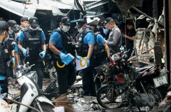 A Thai forensics unit scours the aftermath of a motorcycle bombing which killed three civilians and wounded others at a market in the restive southern Thai province of Yala on January 22, 2018. The motorcycle bomb killed three civilians and wounded 22 others on January 22 at a market in Thailand's insurgency-hit south, officials said, the first such attack on a 'soft target' in the Muslim-majority region for months. / AFP PHOTO / TUWAEDANIYA MERINGING
