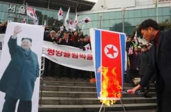 South Korean protesters burn a North Korean flag (R) and a picture (L) of North Korean leader Kim Jong-Un during an anti-North Korea rally outside Seoul station in Seoul on January 22, 2018 as a North Korean delegation arrives at the station. The protest came a day after North Korean delegates arrived in South Korea to prepare for cultural performances during next month's Winter Olympics, in the first visit by Pyongyang officials to the South for four years. / AFP PHOTO / YONHAP / - /  - South Korea OUT / REPUBLIC OF KOREA OUT  NO ARCHIVES  RESTRICTED TO SUBSCRIPTION USE