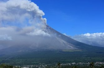 Ash spews from the Mayon volcano as it continues to erupt, seen from the city of Legazpi in Albay province, south of Manila on January 23, 2018. A giant mushroom-shaped cloud shot up from the Philippines' most active volcano on January 22, witnesses and officials said, darkening the skies and raining ash on surrounding communities where tens of thousands have fled an impending eruption. / AFP PHOTO / CHARISM SAYAT