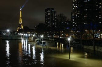 A picture taken late on January 28, 2018 in Paris shows the flooded Quai de Grenelle by the banks of the Seine river, with the Eiffel Tower in background.  The swollen Seine inched even higher on January 28, keeping Paris on alert, with forecasters expecting flooding to peak early on January 29, leaving a lengthy mop-up job. / AFP PHOTO / GEOFFROY VAN DER HASSELT
