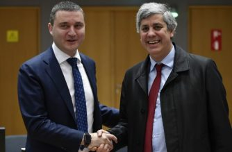Bulgaria's Finance Minister Vladislav Goranov (L) shakes hands with Portuguese Finance Minister and president of Eurogroup Mario Centeno prior to an Economic and Financial Affairs meeting at the EU headquarters in Brussels on January 23, 2018. / AFP PHOTO / JOHN THYS