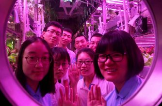 """This handout picture taken and released on January 26, 2018 by the Beihang University News Centre shows Chinese students posing  inside the """"Yuegong-1"""", or """"Lunar Palace-1"""" lunar lab, in Beijing.  The photo shows the team of four students who spent 200 days inside, being joined by a new crew of four, who will stay a further 105 days. Chinese students spent a record-breaking 200 continuous days in a """"lunar lab"""" in Beijing, state media said on January 26, as the country prepares for its long-term goal of putting people on the moon.    / AFP PHOTO / BEIHANG UNIVERSITY NEWS CENTRE / Handout / RESTRICTED TO EDITORIAL USE - MANDATORY CREDIT """"AFP PHOTO / BEIHANG UNIVERSITY NEWS CENTRE"""" - NO MARKETING NO ADVERTISING CAMPAIGNS - DISTRIBUTED AS A SERVICE TO CLIENTS == NO ARCHIVE"""