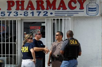 "MIAMI, FL - OCTOBER 14: Law enforment agents stand outside of the Cabana Pharmacy after it was raided by the City of Miami Police Department's Crime Suppression Unit and Florida Department of Health on October 14, 2011 in Miami, Florida. The owner and two of his employees were arrested at the pharmacy after a six-month investigation by law enforcement in connection with selling oxycodone without a prescription. Florida law enforcement continues to crack down on the alleged ""pill mills.""   Joe Raedle/Getty Images/AFP"