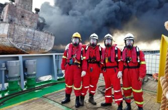 """This handout picture taken on January 13, 2018 and released by the Transport Ministry of China shows four Chinese rescuers posing for a picture before boarding the burning oil tanker """"Shanchi"""" at sea off the coast of eastern China, a day before the Iranian oil tanker burst into flames from end to end and sank. It was reported on January 16 that Beijing has sent its condolences to Iran over the death of 30 sailors from a tanker that sank in the East China Sea, as authorities scrambled to contain a huge spill. / AFP PHOTO / TRANSPORT MINISTRY OF CHINA / Handout / -----EDITORS NOTE --- RESTRICTED TO EDITORIAL USE - MANDATORY CREDIT """"AFP PHOTO / TRANSPORT MINISTRY OF CHINA"""" - NO MARKETING - NO ADVERTISING CAMPAIGNS - DISTRIBUTED AS A SERVICE TO CLIENTS - NO ARCHIVES"""