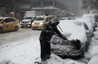 "A man cleans snow from a car during a winter storm in New York on January 4, 2018.    A giant winter ""bomb cyclone"" walloped the US East Coast on Thursday with freezing cold and heavy snow, forcing thousands of flight cancellations and widespread school closures -- and even prompting the US Senate to cancel votes for the rest of the week. / AFP PHOTO / Jewel SAMAD"