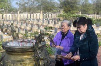 """In this picture taken on January 17, 2018, Nguyen Thi Hoa (L) and Hoang Thi No, who were members of the Perfurme River squad - a top secret female combat unit formed in 1967, place incense sticks at an official cemetery where the graves of four comrades who were killed during the 1968 """"Tet Offensive"""" are located, on the outskirts of Hue. The Tet Offensive, whose 50th anniversary will be marked on January 31, 2018 with an official ceremony in Ho Chi Minh City, was a military failure for the northern forces. But it swung US public opinion decisively away from the anti-communist fight, ultimately leading to the US pullout.   / AFP PHOTO / HOANG DINH Nam / TO GO WITH Vietnam-US-war-history-women,FEATURE by Jenny VAUGHAN"""