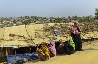 Rohingya Musim refugees sit near a makeshift shelter at Kutupalong refugee camp in Bangladesh's Ukhia district on January 12, 2018. About 655,000 Rohingya have escaped to Bangladesh since August 2017 after the Myanmar army began a campaign of rape and murder in Rakhine state. They joined the more than 200,000 refugees already living in Bangladesh who had fled previous violence in Rakhine. / AFP PHOTO / Munir UZ ZAMAN