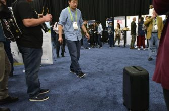 An exhibitor demonstrates the ForwardX Robotics self-driving CX-1 suitcase during the CES Unveiled event on the sidelines of CES 2018 in Las Vegas, Nevada on January 7, 2018. Self-driving cars may take a while to arrive, but the self-driving suitcase is here now. Some of the technologies used in autonomous cars have been adapted in products unveiled at the 2018 Consumer Electronics Show in Las Vegas, to help travelers with the weighty problem of dealing with baggage. / AFP PHOTO / MANDEL NGAN