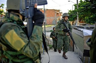 Brazilian military patrol in Jacarezinho favela in Rio de Janeiro on January 18, 2018.  The mandate for Brazil's Military to assist the country's police forces during dangerous raids on traffickers in favelas has been extended until the end of 2018 due to the high rate of murdered police officers and drug related violence.  / AFP PHOTO / CARL DE SOUZA