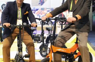 Andrew Koven (L) and Mike Johnson (R) of Swagtron pose on two of the US company's electric bicycle models at the Consumer Electronics Show in Las Vegas on January 9, 2018. / AFP PHOTO / Glenn CHAPMAN
