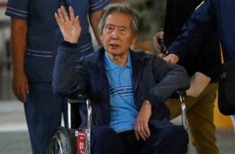 (FILES):  This file photo taken on January 04, 2018 shows Peru's former President Alberto Fujimori waving to supporters as he is wheeled out of the Centenario Clinic in Lima on January 04, 2018, where he was hospitalised  and where he received  pardon from President Kuczynski. / AFP PHOTO / LUKA GONZALES