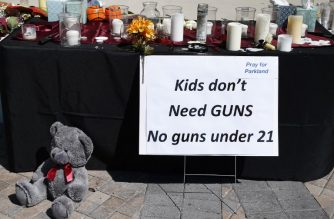 Candles, flowers and stuffed animals serve as a  memorial for the victims of the Marjory Stoneman Douglas High School shooting in a park in Parkland, Florida on February 16, 2018  A former student, Nikolas Cruz, opened fire at the Florida high school leaving 17 people dead and 15 injured. / AFP PHOTO / RHONA WISE