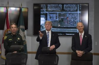 US President Donald Trump (C) speaks with Broward County Sheriff Scott Israel (L) and Florida Governor Rick Scott (R) while visiting first responders at Broward County Sheriff's Office in Pompano Beach, Florida, on February 16, 2018, three days after a mass shooting that claimed 17 lives at a nearby high school.  / AFP PHOTO / JIM WATSON