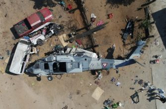 Aerial view of the military helicopter that fell on a van in Santiago Jamiltepec, Oaxaca state, Mexico, on February 17, 2018.  A 7.2-magnitude earthquake rattled Mexico on Friday, causing little damage but triggering a tragedy when a minister's helicopter crash-landed on the way to the epicenter, Oaxaca, killing thirteen people, including three children, on the ground. / AFP PHOTO / MARIO VAZQUEZ