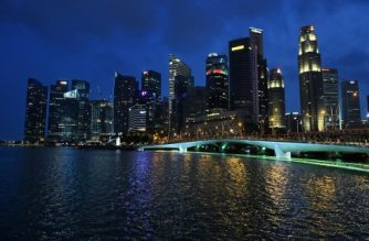 A general view shows the financial business district skyline glitters with lights on before the countdown for Earth Hour campaign in Singapore on March 19, 2016. Millions of people from 178 countries and territories are expected to take part in WWF's Earth Hour this year, with monuments and buildings such as the Eiffel Tower, Taipei 101 and the Empire State Building plunging into darkness for 60 minutes from 8:30pm local time / AFP PHOTO / ROSLAN RAHMAN