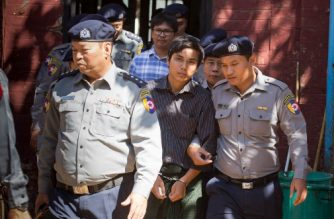 Myanmar police officers escort Reuters journalists Wa Lone (back C) and Kyaw Soe Oo (C) at the northern district court in Yangon on January 23, 2018. A court will decide whether to bail two Reuters journalists accused of breaching Myanmar's secrecy law on February 1, their lawyer said on January 23, raising fears the pair could otherwise face months in detention during convoluted pre-trial hearings. / AFP PHOTO / Aung Kyaw HTET