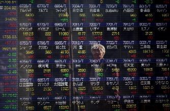 A man looks at a stock indicator showing share prices of Japanese companies in Tokyo on February 7, 2018. Tokyo stocks rebounded slightly in a rollercoaster session on February 7 after Wall Street finished the previous day with solid gains following a global rout. / AFP PHOTO / Behrouz MEHRI
