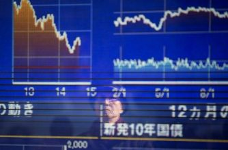 A man looks at a stock indicator showing government bond data report in Tokyo on February 7, 2018. Tokyo stocks rebounded slightly in a rollercoaster session on February 7 after Wall Street finished the previous day with solid gains following a global rout. / AFP PHOTO / Behrouz MEHRI