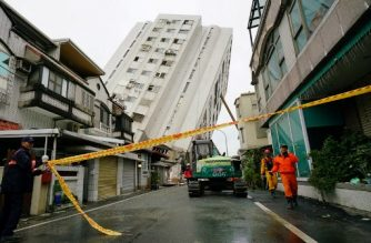 Rescue personnel work near a collapsed building in Hualien on February 8, 2018, after the city was hit by a 6.4-magnitude quake late on February 6. Taiwanese rescuers on February 8 braved aftershocks coursing through a dangerously leaning apartment block that was partially toppled by a deadly earthquake, as their search for survivors uncovered three more bodies. / AFP PHOTO / PAUL YANG