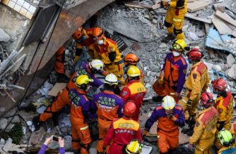 The second of two bodies is removed from the Yun Tsui building, which is leaning at a precarious angle, in the Taiwanese city of Hualien on February 9, 2018, after the city was hit by a 6.4-magnitude quake late on February 6. Taiwan began demolishing three dangerously damaged buildings on February 9 as rescue workers combed the rubble of a hotel in a last-ditch effort to find seven people still missing after a deadly earthquake. / AFP PHOTO / Anthony WALLACE