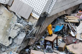 A rescue worker clears debris to make way for the recovery of the dead bodies of a Hong Kong Canadian couple from the Yun Tsui building, which is leaning at a precarious angle, in the Taiwanese city of Hualien on February 9, 2018, after the city was hit by a 6.4-magnitude quake late on February 6. After hours of painstaking search efforts, Taiwanese rescue workers pulled two more bodies from the flattened remains of a hotel February 9, bringing the death toll from a deadly 6.4-magnitude quake to 12.  / AFP PHOTO / Anthony WALLACE