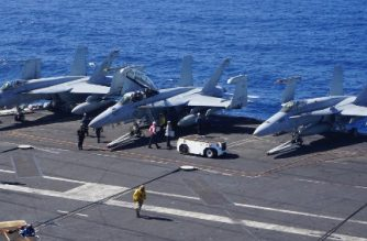 Sailors work next to F-18 Hornet fighter jets on the flight deck of the aircraft carrier USS Carl Vinson on February 14, 2018, as the carrier strike group takes part in a routine deployment mission in the South China Sea, one hour away from Manila.  With a deafening roar and earthshaking vibrations, fighter jets zoomed off US carrier USS Carl Vinson as it navigated in the waters of the disputed South China Sea in what its admiral said February 14 was a tangible sign of American presence in the region. / AFP PHOTO / AYEE MACARAIG