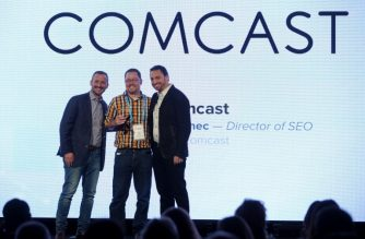 NEW YORK, NY - NOVEMBER 01: Director of SEO Sean Kainec (C) accepts the Digital Knowledge Innovator of the Year award on behalf of Comcast from Yext Co-Founder & President Brian Distelburger and Yext EVP of Partner Jonathan Cherins onstage at the ONWARD17 Conference- Day 1 on November 1, 2017 in New York City.   Brad Barket/Getty Images for ONWARD17/AFP