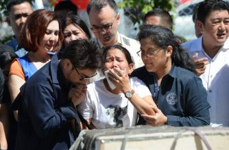 Jessica (C), sister of Filipina overseas worker Joanna Demafelis whose body was found inside a freezer in Kuwait, cries in front of a wooden casket containing her sister's body shortly after its arrival at the international airport in Manila on February 16, 2018, while Philippine Foreign Secretary Alan Peter Cayetano (C-behind w/glasses) looks on. / AFP PHOTO / TED ALJIBE