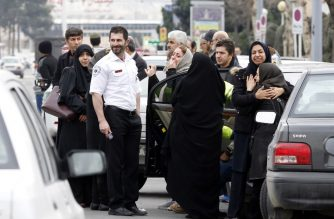 Relatives of Iranian passengers, onboard the Aseman Airlines flight EP3704, react as they gather in front of a mosque near Tehran's Mehrabad airport on February 18, 2018.  All 66 people on board an Iranian passenger plane were feared dead after it crashed into the country's Zagros mountains, with emergency services struggling to locate the wreckage in blizzard conditions.  / AFP PHOTO / ATTA KENARE