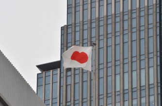 Japanese national flag flies on the roof of a building in Tokyo on November 14, 2016.  / AFP PHOTO / KAZUHIRO NOGI