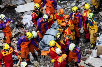 Rescue workers remove the second of two bodies of a Hong Kong Canadian couple from the Yun Tsui building, which is leaning at a precarious angle, in the Taiwanese city of Hualien on February 9, 2018, after the city was hit by a 6.4-magnitude quake late on February 6. After hours of painstaking search efforts, Taiwanese rescue workers pulled two more bodies from the flattened remains of a hotel February 9, bringing the death toll from a deadly 6.4-magnitude quake to 12.  / AFP PHOTO / Anthony WALLACE