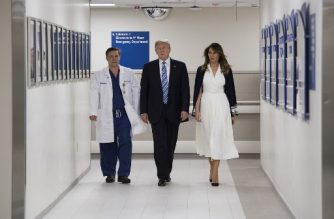 US President Donald Trump speaks with doctor Igor Nichiphorenko (L) and First Lady Melania Trump while visiting first responders at Broward Health North hospital Pompano Beach, Florida, on February 16, 2018.  US President Donald Trump and First Lady Melania Trump visited a Florida hospital to offer their respects to the victims of a mass shooting that claimed 17 lives at a nearby high school.   / AFP PHOTO / JIM WATSON