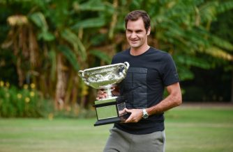 Switzerland's Roger Federer holds the Australia Open trophy at Government House as he poses for pictures following his win in the Australian Open in Melbourne on January 29, 2018.  / AFP PHOTO / PETER PARKS
