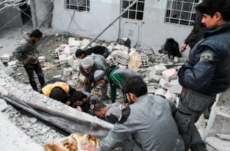 Syrian civil defense volunteers attempt to rescue people from under debris and destruction following a reported regime air strike in the rebel-held besieged town of Douma in the eastern Ghouta region, on the outskirts of the capital Damascus, on February 15, 2018.  / AFP PHOTO / Hamza Al-Ajweh