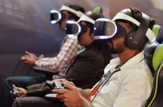 Gamers wearing virtual reality (VR) glasses play games at a stall during the India Gaming Show South 2018 expo at the Bangalore International Exhibition Centre on January 19, 2018. India Gaming Show South 2018, an International gaming, animation and infotainment event aims to reach out to professional gamers, developers and audiences at large. / AFP PHOTO / MANJUNATH KIRAN