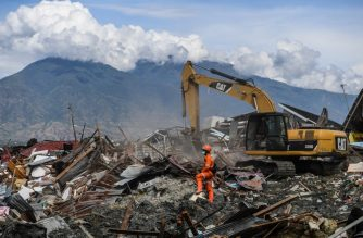 """An Indonesian search and rescue team uses heavy equipment to recover bodies from the debris in Petobo in Central Sulawesi on October 8, 2018, following the September 28 earthquake and tsunami. - Nearly 2000 bodies have been recovered from Palu since an earthquake and tsunami struck the Indonesian city, an official said on October 8, warning the number would rise with thousands still missing. (Photo by MOHD RASFAN / AFP) / """"The erroneous mention[s] appearing in the metadata of this photo by MOHD RASFAN has been modified in AFP systems in the following manner: [dateline as Petobo] instead of [Palu]. Please immediately remove the erroneous mention[s] from all your online services and delete it (them) from your servers. If you have been authorized by AFP to distribute it (them) to third parties, please ensure that the same actions are carried out by them. Failure to promptly comply with these instructions will entail liability on your part for any continued or post notification usage. Therefore we thank you very much for all your attention and prompt action. We are sorry for the inconvenience this notification may cause and remain at your disposal for any further information you may require."""""""