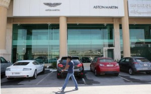 A man walks in front of cars parked outside an Aston Martin showroom in Doha, October 19, 2013. Credit: Reuters/Fadi Al-Assaad