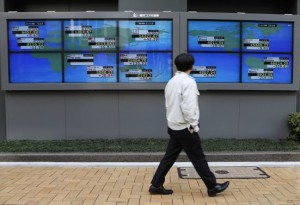 A pedestrian walks past electronic boards showing various countries' share prices outside a brokerage in Tokyo February 6, 2014. Asian shares took a tentative step forward from five-month lows on Thursday, with investors hoping the European Central Bank (ECB) and upcoming U.S. jobs data can calm nerves strained by the emerging market selloff.   REUTERS/Toru Hanai